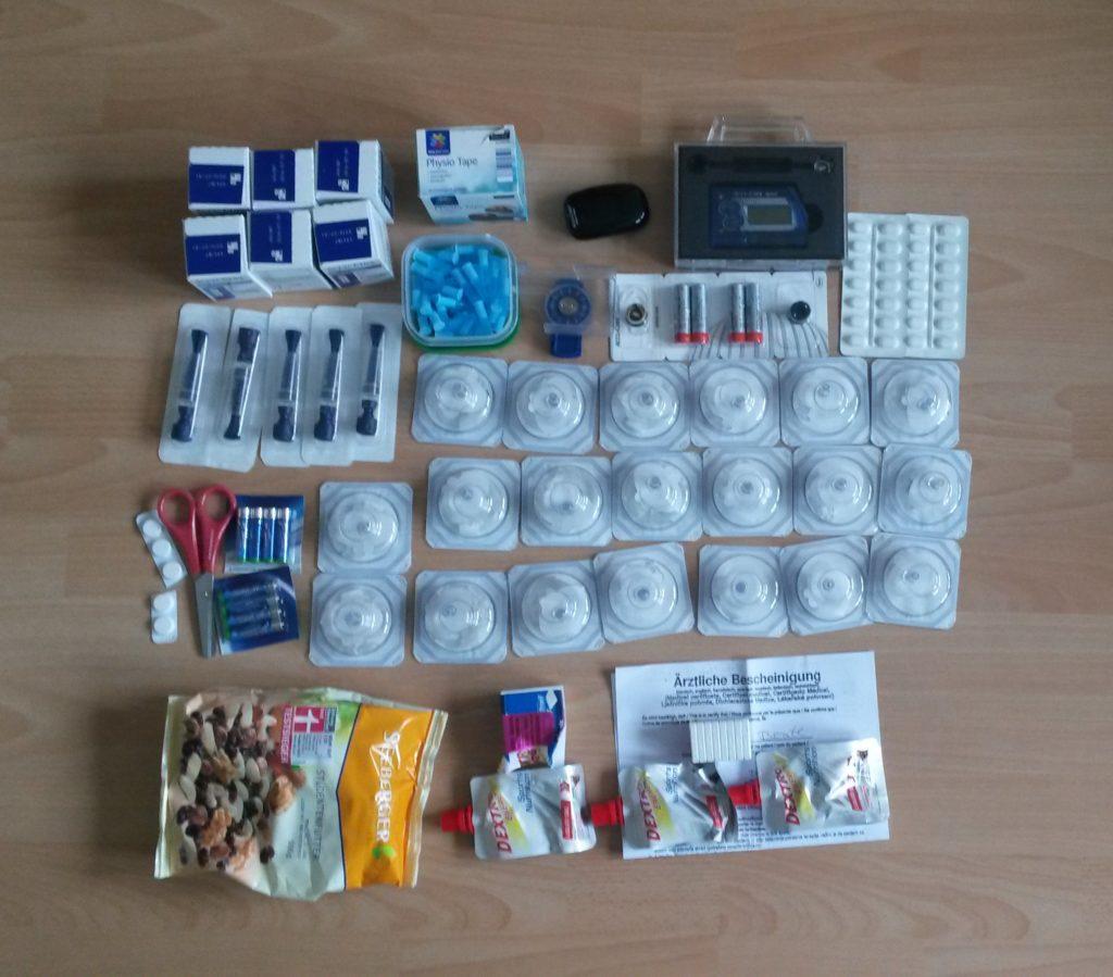 Bildbeschreibung: Diabetesutensilien (Katheter, Teststreifen, Ersatzpumpe, Hypo-BE)